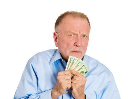 possessive: Closeup portrait, greedy senior executive, CEO, boss, old corporate employee, mature man, holding dollar banknotes tightly, isolated white background. Negative human emotion facial expression