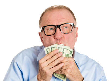 possessive: Closeup portrait, greedy senior executive, CEO, boss, old corporate employee, mature man, holding, kissing dollar banknotes in hand, isolated white background. Negative human emotion facial expression