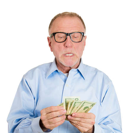 Closeup portrait, greedy, nerd senior executive, CEO, boss, old corporate employee, mature man, counting dollar banknotes carefully, isolated white background. Negative human emotion facial expression