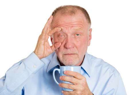 Closeup portrait senior mature, tired, falling asleep business man holding cup, struggling not to crash, stay awake, keep eyes opened, isolated white background. Human emotion, facial expression photo