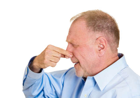 stinks: Closeup side view portrait senior mature man, disgust on face, pinching nose, something stinks, very bad smell, odor, situation, isolated white background. Negative emotion facial expression feeling