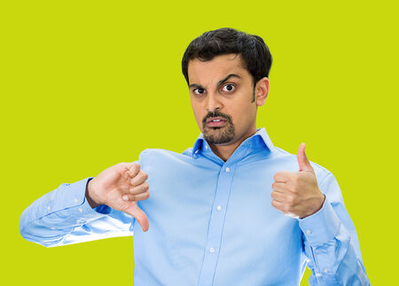 Closeup portrait, confused, young man pointing in two different directions, not sure if good or bad, showing thumbs up, down simultaneously, isolated green background. Emotion, face expression
