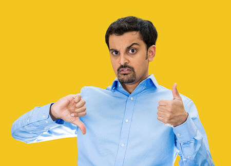 befuddled: Closeup portrait, confused, young man pointing in two different directions, not sure if good or bad, showing thumbs up, down simultaneously, isolated yellow background. Emotion, face expression