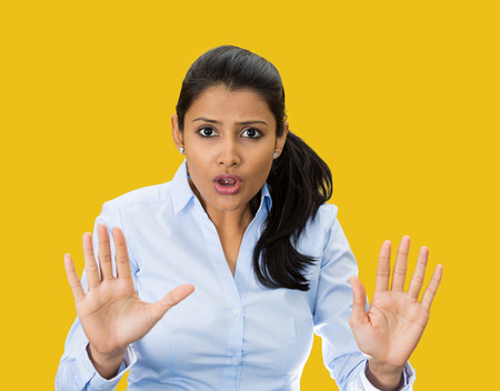 Closeup portrait, furious, mad, angry, annoyed, displeased young woman raising hands up to say no, stop right there, isolated yellow background. Negative human emotion facial expression sign symbol 스톡 콘텐츠