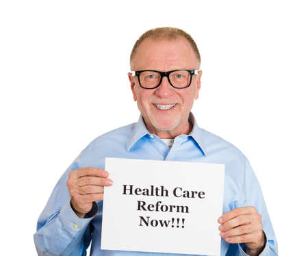 hmo: Closeup portrait, happy senior mature business man, corporate employee holding health care reform now! sign, isolated white background. Government, federal politics, congress, insurance policy debate Stock Photo