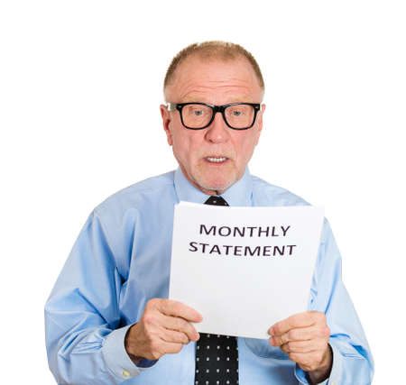 bank records: Closeup portrait, sad, shocked funny looking senior mature nerd man upset, monthly statement, isolated white background. Negative human emotion facial expression feelings. Financial crisis, bad news