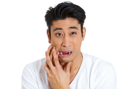 Closeup portrait of young man with sensitive tooth ache bridge crown problem pain touching outside mouth with hand, isolated white background. Negative human emotions, facial expressions, feelings photo