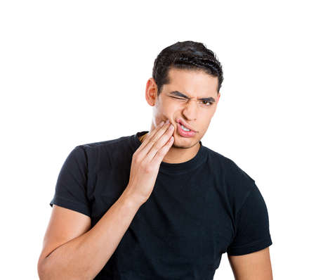 abscess: Closeup portrait young man with sensitive toothache bridge problem about to cry from oral pain touching outside mouth with hand, isolated white background. Negative emotion facial expression feeling Stock Photo