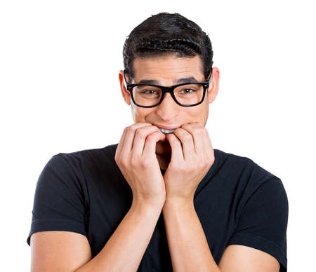 perfectionist: Closeup portrait, young nerdy guy, anxious man with big glasses, biting finger nails craving something scared, looking at you, isolated white background. Negative human emotions, facial expressions