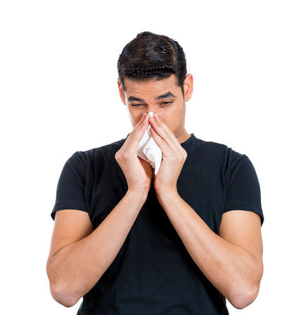 miserable: Closeup portrait, sick young man student, worker with allergy or germs cold, blowing his nose with kleenex, looking miserable unwell very sick, isolated white background. Flu season, vaccine, Stock Photo