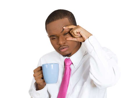 eyes opened: Closeup portrait young, tired, falling asleep business man holding cup coffee, struggling not to crash, stay awake, keep eyes opened, isolated white background. Human emotion, facial expressions