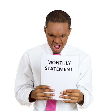 bank records: Closeup portrait sad, shocked funny looking young man, disgusted at monthly statement, isolated white background. Negative human emotion facial expression feeling, reaction. Financial crisis, bad news Stock Photo