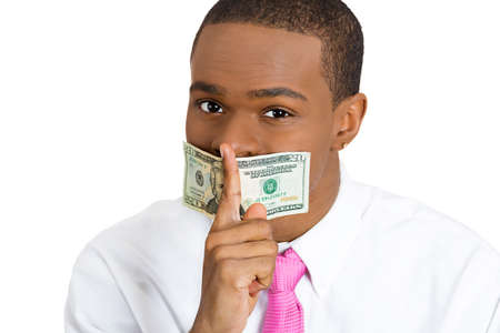 under paid: Closeup portrait handsome corrupt guy in shirt, with twenty dollar bill taped to mouth, showing shh sign, isolated white background. Bribery concept in politics, business, diplomacy. Facial expression Stock Photo
