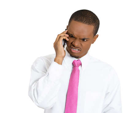 Closeup portrait, young, serious, angry business man, corporate employee, student talking on cell phone, having unpleasant conversation, isolated white background. Negative human emotions. photo
