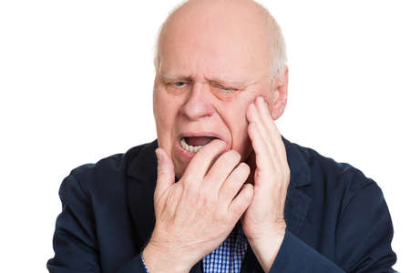 gingivitis: Closeup portrait elderly business man with tooth ache crown problem cavity crying from pain touching outside mouth with hand isolated white background. Negative human emotion facial expression feeling Stock Photo