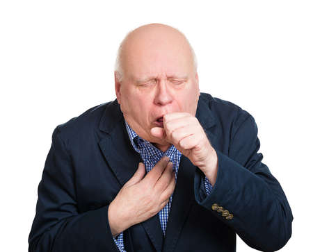 asthma: Closeup portrait, sick old man, senior worker, elderly executive guy, having severe infectious cough, holding chest, raising fist to mouth looking miserable unwell, isolated white background.