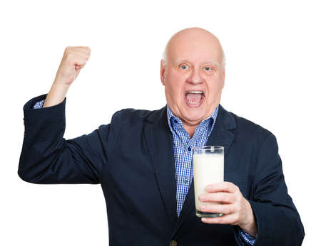 senior man: Closeup portrait, smiling, excited, senior, mature man flexing muscle, holding glass of milk, isolated white background. Positive human emotion facial expression feelings, attitude, perception Stock Photo