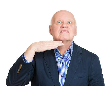 cut off head: Closeup portrait  senior, mature man gesturing with hand to stop talking, cut it out, he will take your head off, isolated white background. Negative emotions, facial expressions, feelings, reaction Stock Photo