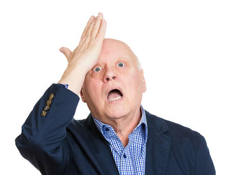 duh: Closeup portrait, goofy, funny face, senior mature man slapping hand on head to say duh, oops, isolated white background. Negative human emotion facial expression feelings, body language