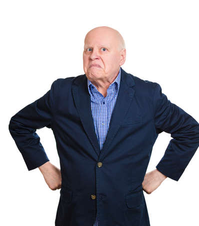 face off: Closeup portrait angry, mad, annoyed, senior mature business man, unhappy, looking at you, hands on waist isolated white background. Human emotion, face expression, attitude, conflict resolution Stock Photo