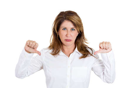 disapproval: Closeup portrait, unhappy business woman, wife, giving thumbs down gesture looking with negative expression and disapproval, isolated white background. Human emotion facial expression, feeling Stock Photo