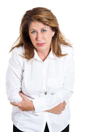 doubled: Closeup portrait, mature, stressed woman, placing hands on stomach having bad aches, pains, isolated white background. Food poisoning influenza cramps. Negative emotion, facial expression, reaction Stock Photo