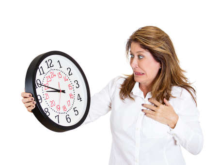 Closeup portrait mature, woman, worker, holding clock looking anxiously, pressured by lack, running out of time, isolated white background. Human face expression, emotion, reaction, corporate life Stock Photo