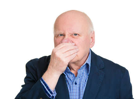 stinks: Closeup portrait, senior mature man, disgust face, pinch nose, looks funny, something stinks, very bad smell, isolated white background. Negative emotion, facial expression, feeling reaction