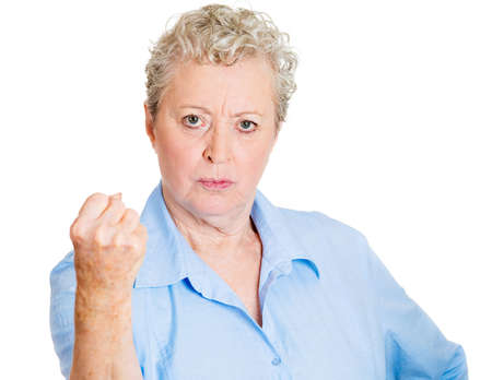 cranky: Closeup portrait, angry, cranky, upset, senior mature woman, business worker, fist up about to give you knuckle sandwich, isolated white background. Negative human emotion facial expression feeling