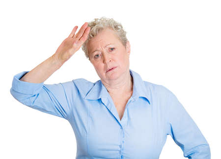 sad heart: Closeup portrait, annoyed, cute senior mature woman placing back hand on forehead thinking, oh the tragedy of it all, woe is me, isolated white background. Negative human emotion, facial expression Stock Photo