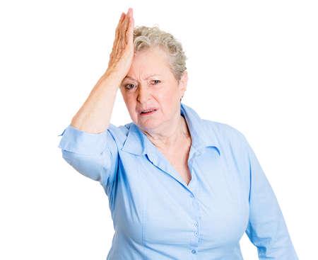 duh: Closeup portrait, goofy, senior mature, woman slapping hand on head, duh, doh, isolated white background. Negative human emotion facial expression feelings, body language