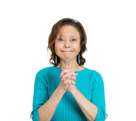 to implore: Closeup portrait, senior mature woman gesturing with clasped hands, pretty please with sugar on top, isolated white background. Positive emotion facial expression feelings, sign symbol, body language.