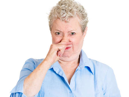 stinks: Closeup portrait old lady, senior executive, grandmother, disgust on her face, pinching nose something stinks, displeased with situation, isolated white background. Interpersonal conflict Stock Photo