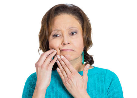 Closeup portrait, elderly business woman with tooth ache, crown problem, cavity pain, touching outside mouth with hand, isolated white background. Negative human emotion facial expression feeling photo