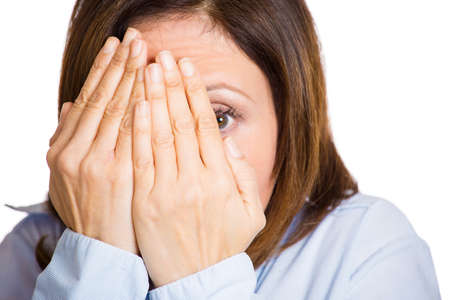monster movie: Closeup portrait, mature, scared, terrified, horrified shocked woman peeking through covered hand, cant believe what she sees, isolated white background. Negative emotion facial expression feelings. Stock Photo