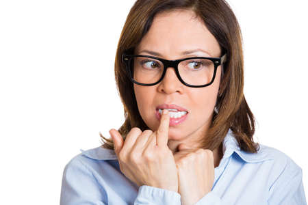 perspiration: Closeup portrait nervous nerd, woman in black glasses, biting fingernails craving something, anxious, isolated white background. Negative human emotion, facial expression, feeling reaction Stock Photo