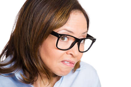 inhibited: Closeup portrait, mature nerdy looking woman with black glasses, very timid, suspicious shy and anxious looking at camera, isolated white background. Mental health, emotion facial expression feeling Stock Photo