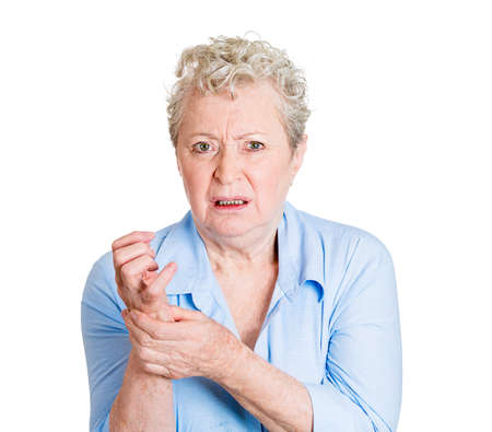 Closeup portrait, elderly, senior corporate employee, old woman looking miserable in great excruciating hand pain ache, isolated white background. Geriatrics health issues, problems. Osteoarthritis.