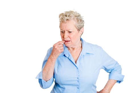 deficient: Closeup portrait, senior mature woman, finger in mouth, trying to remember something, isolated white background. Positive human emotion facial expression feelings, attitude, reaction situation
