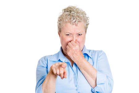 stinks: Closeup portrait old lady, senior executive, grandmother, disgust on face, pinching nose something stinks, pointing at you, displeased with situation, isolated white background. Interpersonal conflict Stock Photo