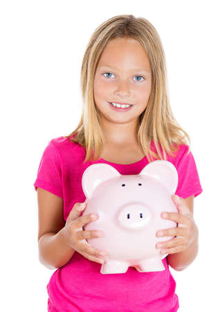 Closeup portrait, young smiling girl holding, hugging piggy bank filled with money, isolated white background. Smart currency financial investment wealth decisions. Budget management and savings photo