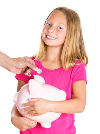 Closeup portrait, young smiling girl holding piggy bank as someone deposits money, isolated white background. Smart currency financial investment wealth decisions. Budget management and savings photo