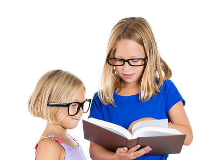 self study: Closeup portrait, adorable, cute, beautiful children, sisters with black glasses sharing and reading a brown book, isolated white background. Positive human emotion facial expression, feelings
