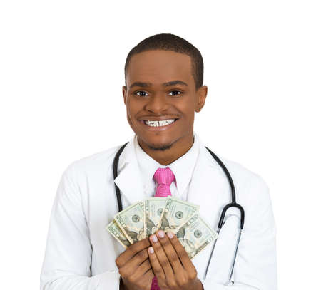 doctor money: Closeup portrait, happy, health care professional, business man, doctor holding dollar bills, cash, money in hand, isolated white background. Human emotions, facial expressions, attitude, finances  Stock Photo