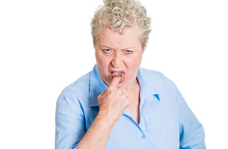 Closeup portrait, unhappy senior mature woman, finger in mouth, wanting to puke, looking with disapproval facial expression, isolated white background. Negative human emotion  photo