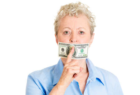 sweeten: Closeup portrait, senior mature woman, twenty dollar bill taped to mouth shut, showing shhh sign, isolated white background. Bribery concept in politics, business, and diplomacy. Stock Photo