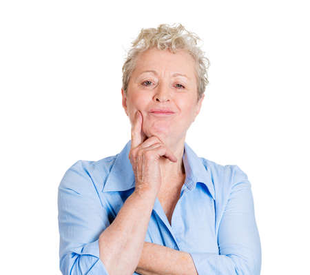 thinking of you: Closeup portrait charming, smiling, joyful, happy senior mature woman looking at you, daydreaming, thinking something, isolated white background. Positive human emotion facial expression feeling Stock Photo