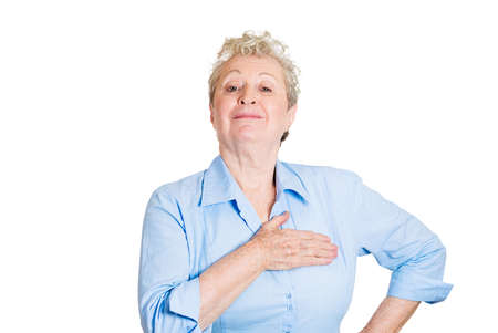 hand on chest: Closeup portrait, proud, happy senior mature woman pledging allegiance, hand on chest, head up, isolated white background. Positive human emotion facial expression feelings.