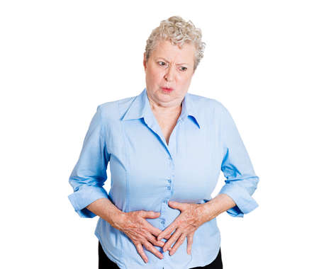 incontinence: Closeup portrait old business woman, elderly boss, corporate worker, unhealthy grandmother doubling over in stomach pain, isolated white background. Human emotions, facial expressions. Acute abdomen