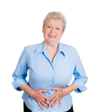 bladder cancer: Closeup portrait old business woman, elderly boss, corporate worker, unhealthy grandmother doubling over in stomach pain, isolated white background. Human emotions, facial expressions. Acute abdomen